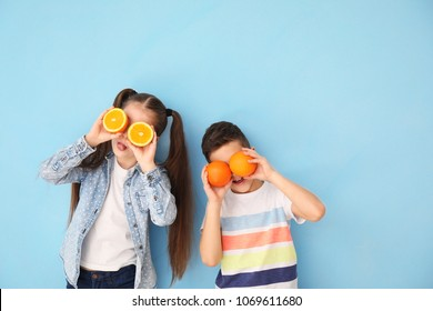 Funny little children with citrus fruit on color background