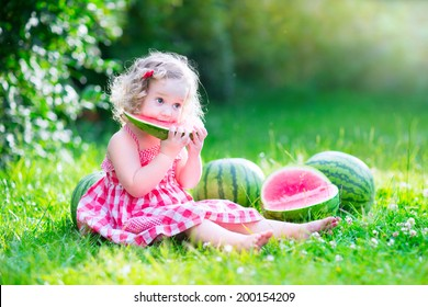 Funny little girl, adorable toddler with curly hair wearing a red dress, eating watermelon, healthy fruit snack, playing in a sunny garden on a hot summer day
