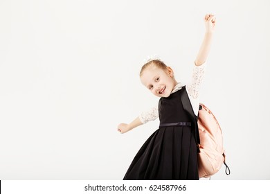 Funny little girl with big backpack jumping and having fun against white background. School concept. Back to School. School's out for summer. Celebrating the end of another successful school year