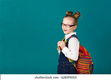 Funny little girl with big backpack jumping and having fun against turquoise wall. School concept. Back to School. School's out for summer. Celebrating the end of another successful school year