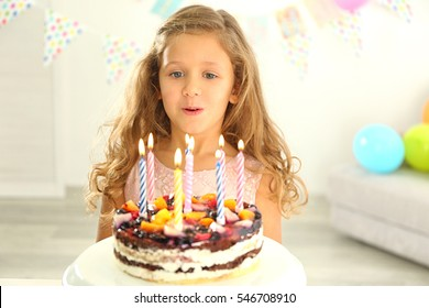 Funny little girl with birthday cake at home