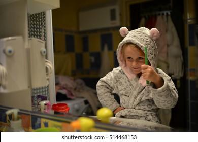 Funny little girl brushing teeth in bath.