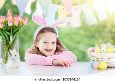 Funny little girl in bunny ears at breakfast on Easter morning at table with Easter eggs basket. Kids celebrating Easter. Children on Easter egg hunt. Home decoration - pastel bunny banner and flowers