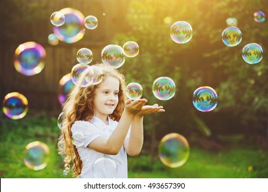 Funny little girl catching soap bubbles in the summer on nature. Background toning instagram filter. Happy childhood concept.