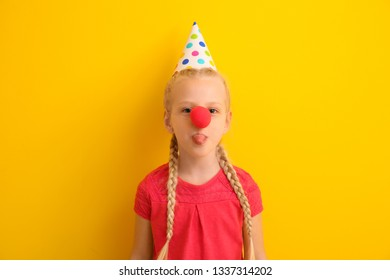 Funny little girl with clown nose and party hat on color background. April fools' day celebration