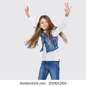 Funny little girl dancing with arms up isolated on white background