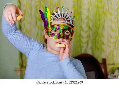 Funny little girl day party Purim celebration concept with carnival mask with hamantaschen cookies or hamans ears
