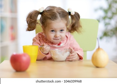 Funny little girl eating yogurt at home or daycare