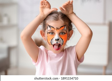 Funny little girl with face painting at home