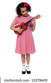 Funny little girl with a guitar isolated on white background.