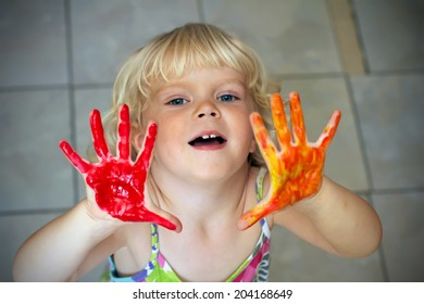 Funny little girl with hands in the paint