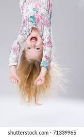 Funny little girl hanging with her foot