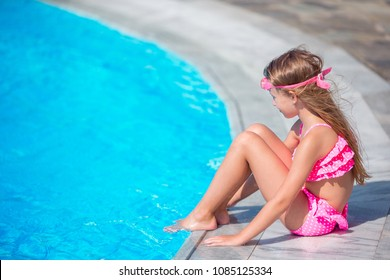 Funny little girl have a fun with a splash near swimming pool
