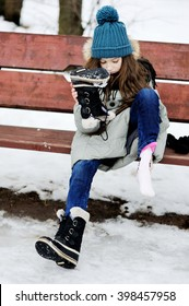 Funny little girl having fun in beautiful winter park and put off snow from the boots