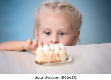 Funny little girl hiding behind white table and looking at tasty cake