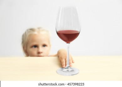 Funny little girl hiding behind table and looking at wine glass