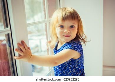 Funny little girl hold on big window