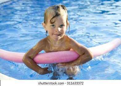 Funny little girl learning to swim with pool noodle