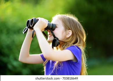 Funny little girl looking through binoculars on sunny summer day. Child exploring distant views.