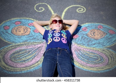 Funny little girl lying on asphalt with painted butterfly wings. Concept of a imagination