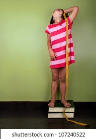 a funny little girl measuring herself with a yellow meter up in to books