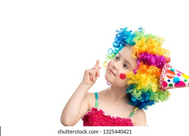 Funny little girl in multicolored clown wig pointing up on blank space, isolated on a white background, space for text