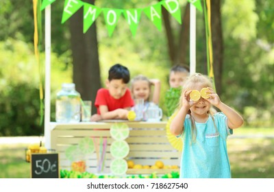 Funny little girl near lemonade stand in park