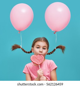 Funny little girl on background of bright blue wall. Beautiful child is having fun with balloon and lollipop. Pink and turquoise colors.