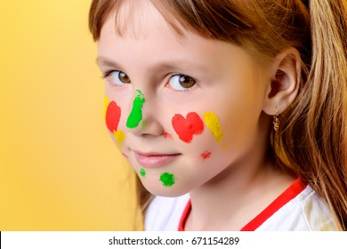 Funny little girl with paints on her face. Drawing. Yellow background.