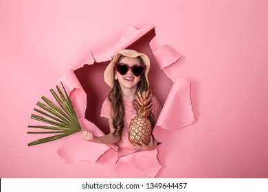 funny little girl peeking out of a hole in a beach hat and heart-shaped glasses with pineapple in her hands and tropical leaves, on a colored background, space for text, Studio shooting