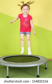 Funny little girl with pigtails jumping on a small trampoline