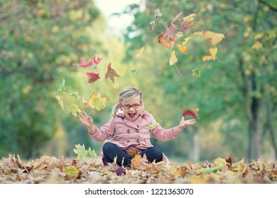 funny little girl is playing in autumn park