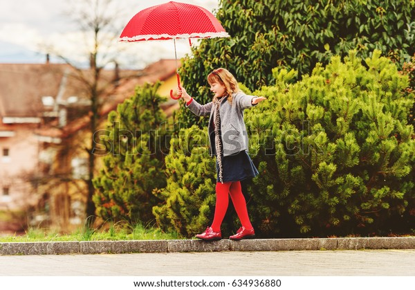 Funny little girl playing outdoors with big red polkadot umbrella