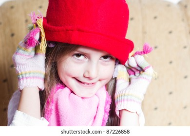 Funny little girl in red hat and with gloves on her hands