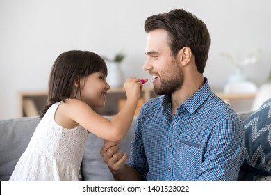 Funny little girl relax have fun with young father color paint lips with lipstick, happy smiling dad and preschooler daughter entertain enjoy spending time together do makeup relaxing on couch