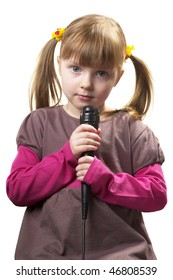Funny little girl singing with microphone isolated over white background