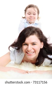 Funny little girl sits on mother which lying on white fluffy rug, mother in focus