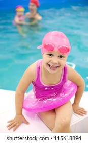 Funny little girl sitting near  swimming  pool in an pink life preserver