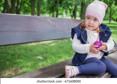 Funny little girl sitting in the park