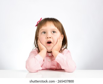 funny little girl sitting in a pink shirt and a bow on her head on a white table. portrait on white background.