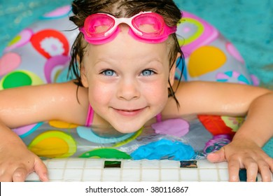 Funny little girl swimming in a pool in colorful life preserver