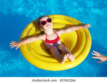 Funny little girl swims in a pool in an yellow life preserver