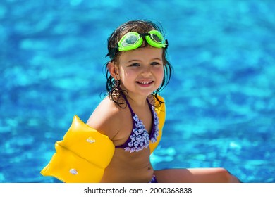Funny little girl swims in a pool in yellow inflatable armbands