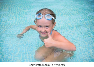 funny little girl swims in the pool