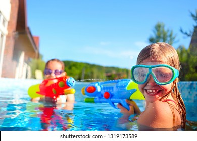 Funny little girls playing with water guns wearing pool masks on summer day in the pool