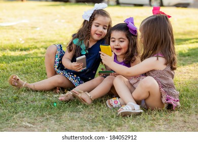 Funny little girls sharing some stuff from their smart phones and having fun