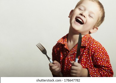 Funny Little Handsome Boy with Fork and Knife. Hungry Child. Smiling Kid. Want to eat