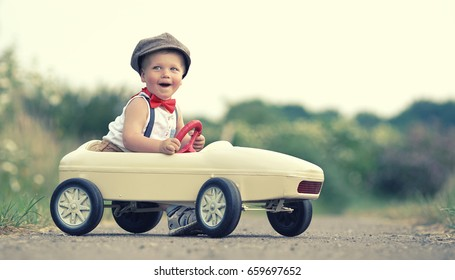 Funny little happy boy having fun and driving toy race car