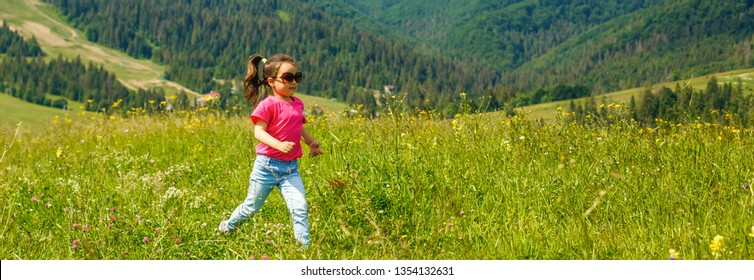 funny little happy girl on the mountain top. Freedom, little girl playing on meadow. Travel, lifestyle concept