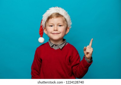 Funny little hipster in red Santa hat with finger pointed up. Child with Christmas gift. Stylish boy kid against blue wall at home. Happy xmas and New Year, winter holiday concept